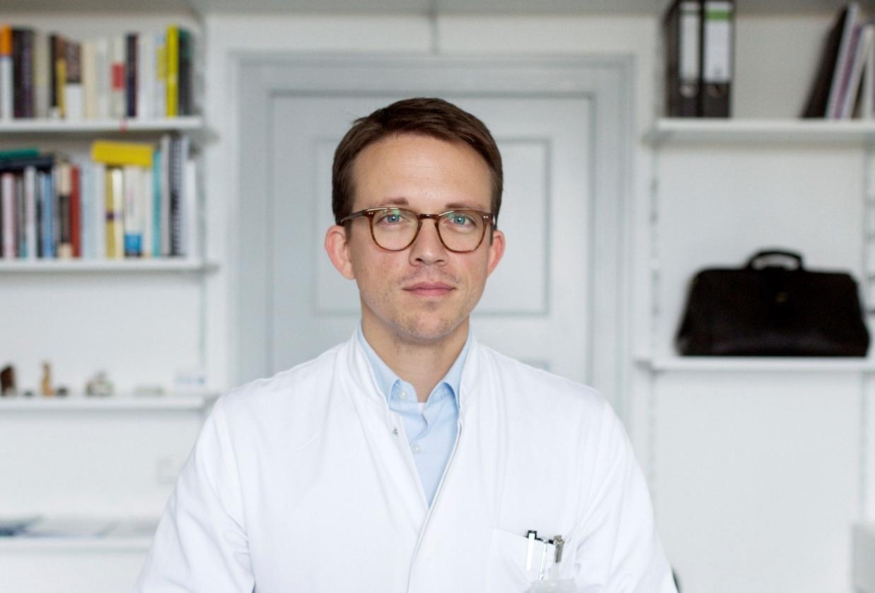 Leonhard Schilbach steht in Arztkittel vor einem weißen Bücherregal